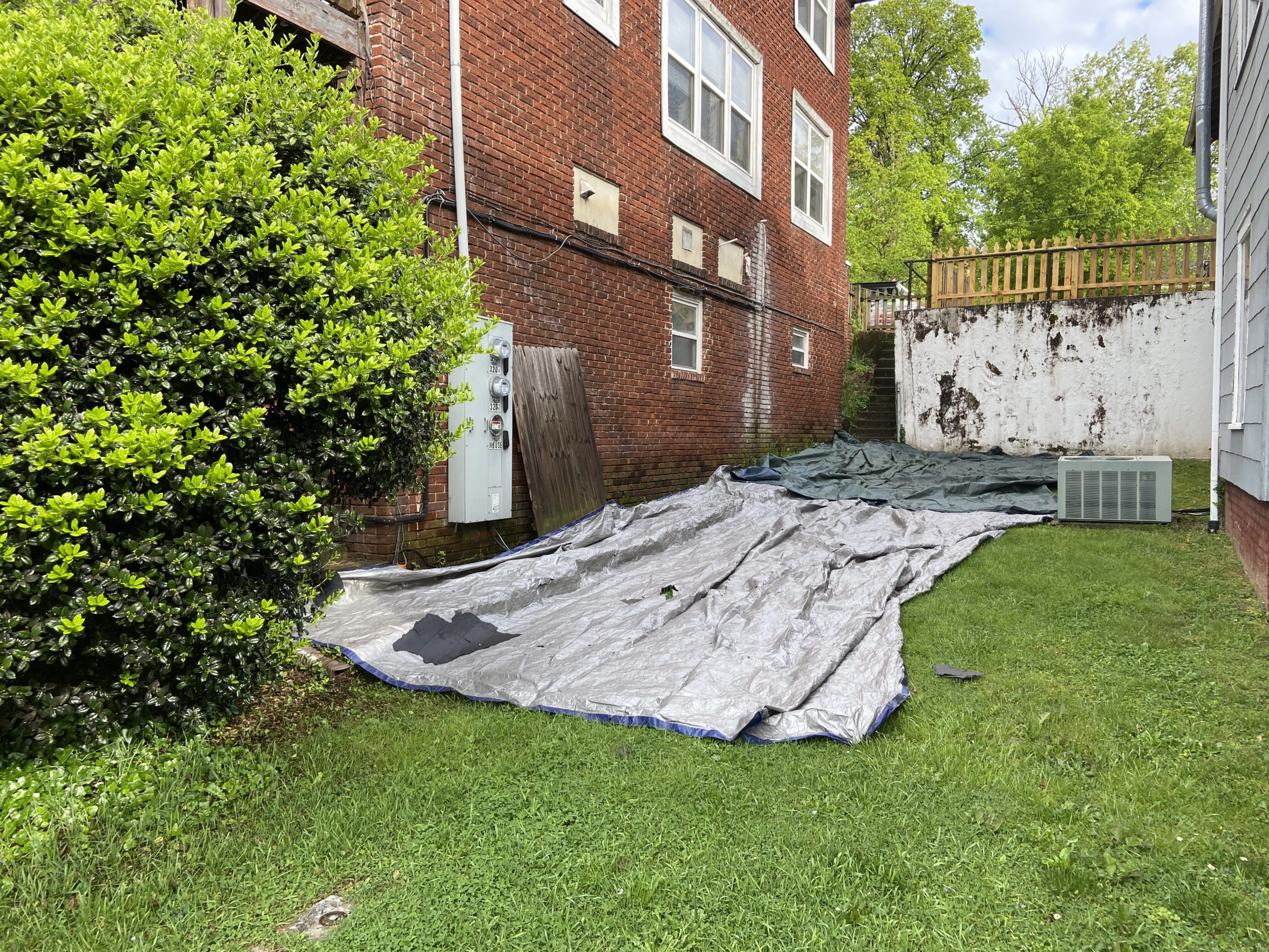 This is a view of tarps that are laid on the ground around the house for protection.