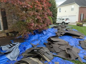 This is a view of blue tarps on the ground with old shingles that have been removed from the roof.
