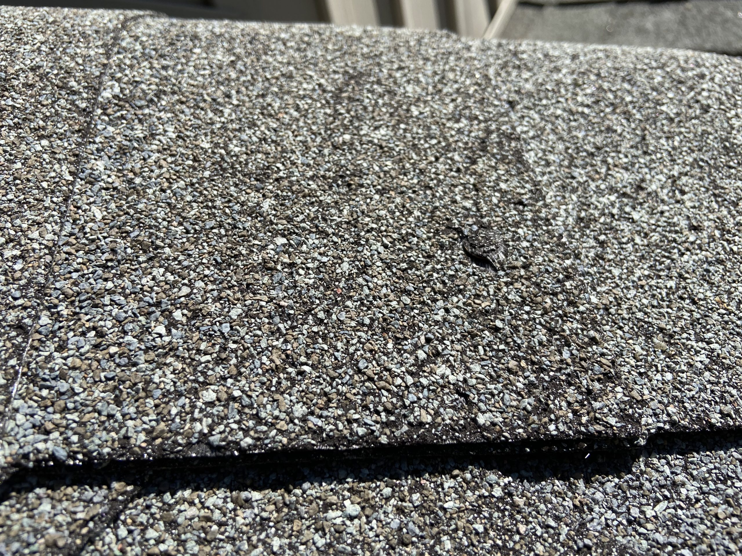 This is a very close view of a ridge cap shingle that is damaged.