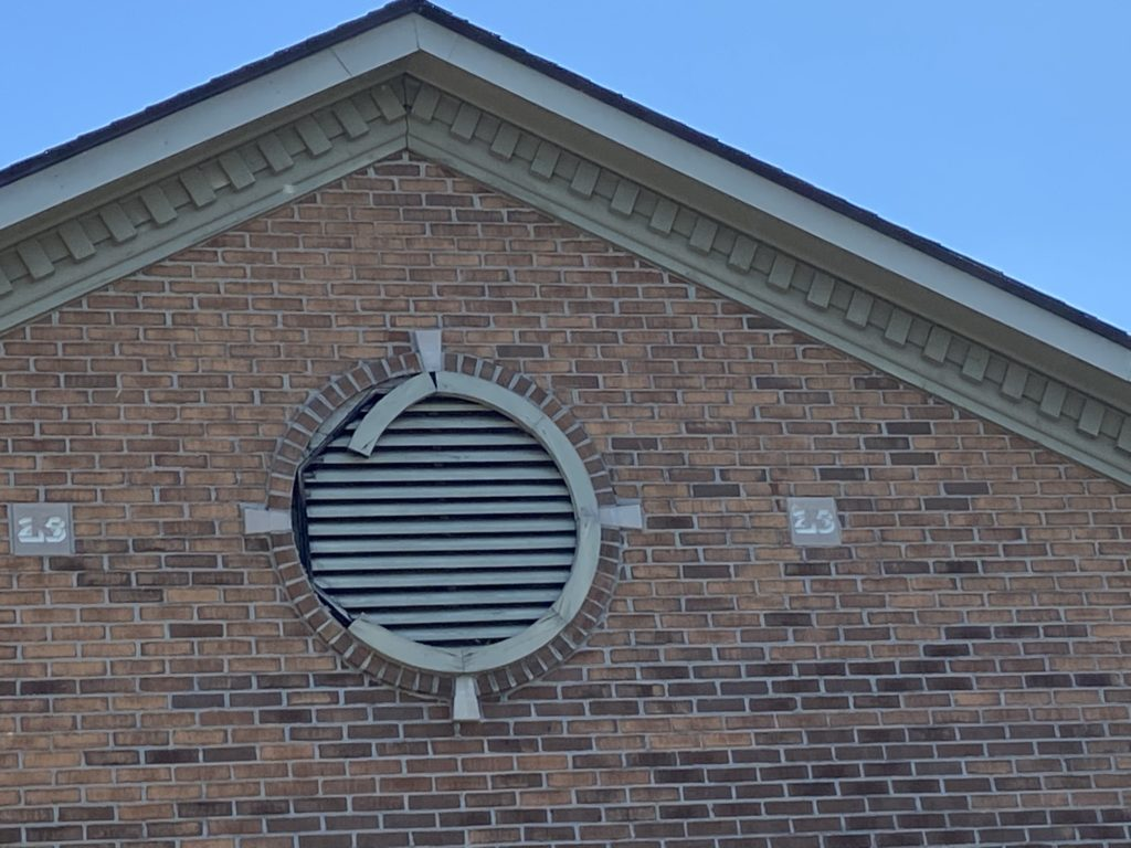 This is a view of a circular gray vent around brick.