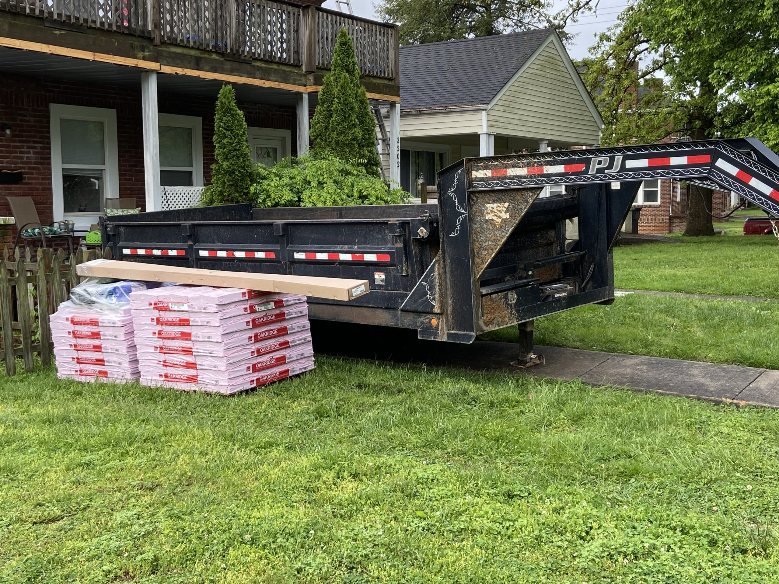 This is the view of the shingle bundles and dump trailer delivered to the home prior to roofing.