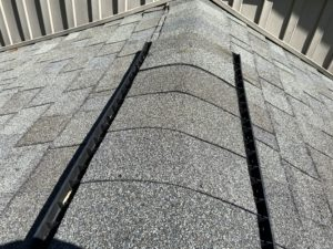 This is a view of the ridge of the roof with ridge cap shingles.