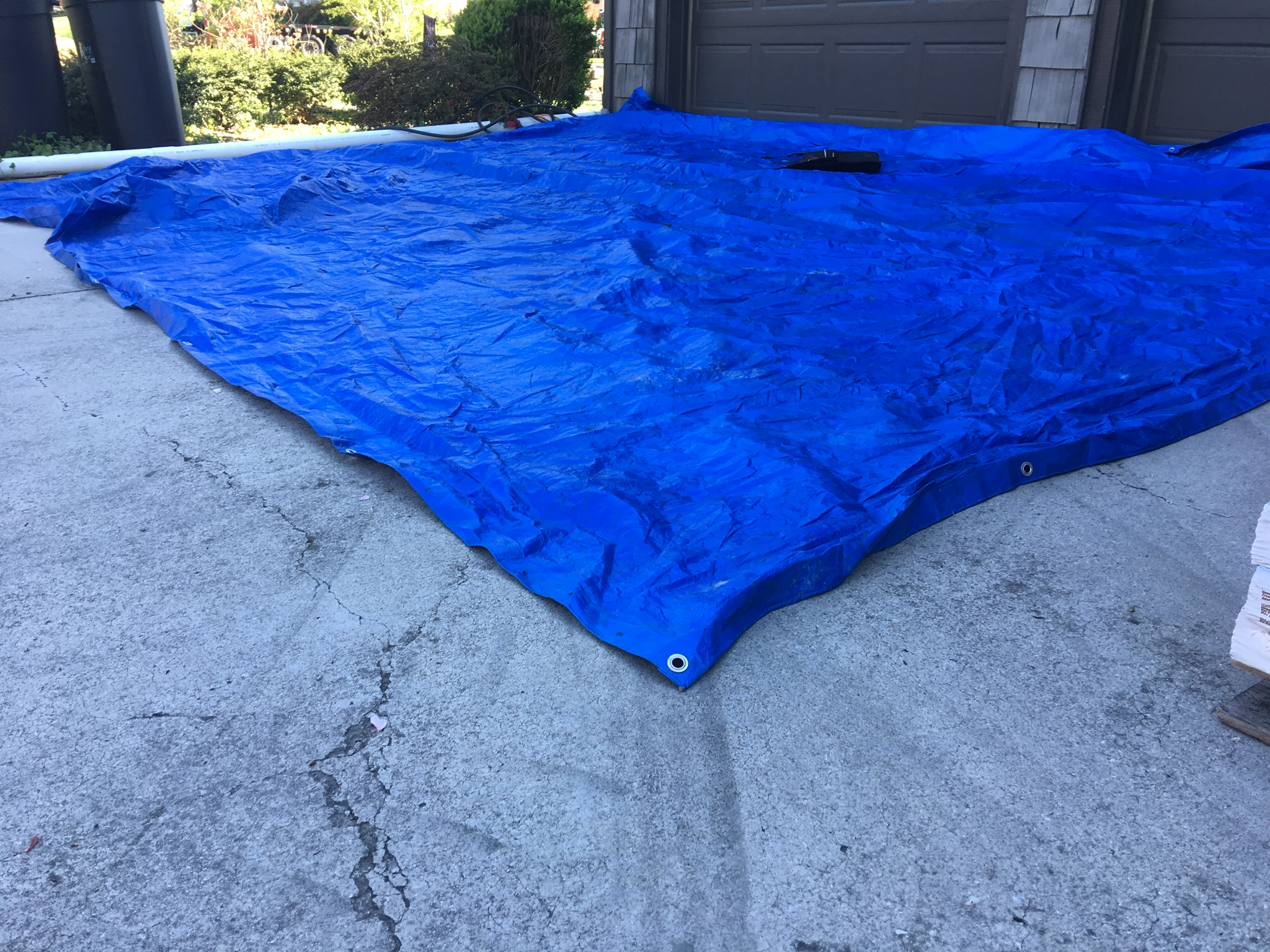 A blue tarp was placed on the concrete driveway in preparation of the materials being delivered to help protect the driveway.
