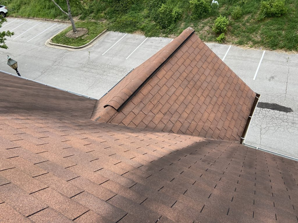 This is a view looking down from the ridge of the roof at weathered, stained looking shingles.