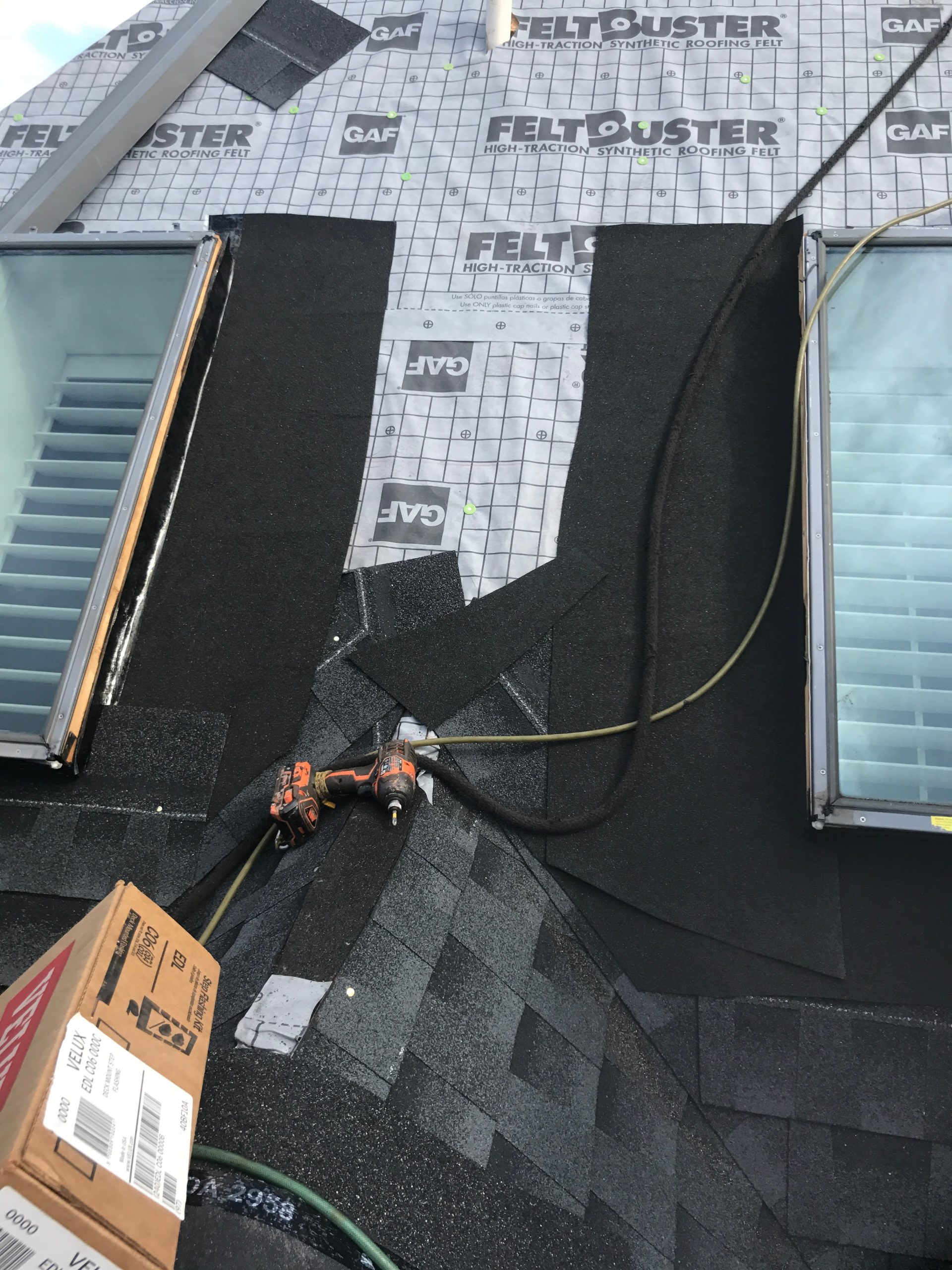 This is a view of installation of flashing at the skylight you can also see the GAF Feltbuster on the roof.