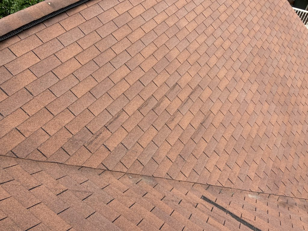This is an image of the roof near the ridge showing creased shingles.