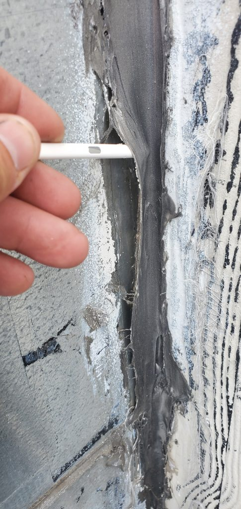 A close up image of the EPDM at the wall that is not sealed and tearing away from wall.