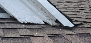 This is a close up view of white roof dormer that is damage.