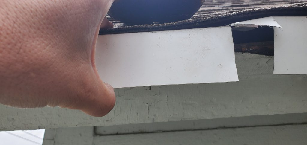 A close up view of white drip edge with the incorrect nails used on this roof.