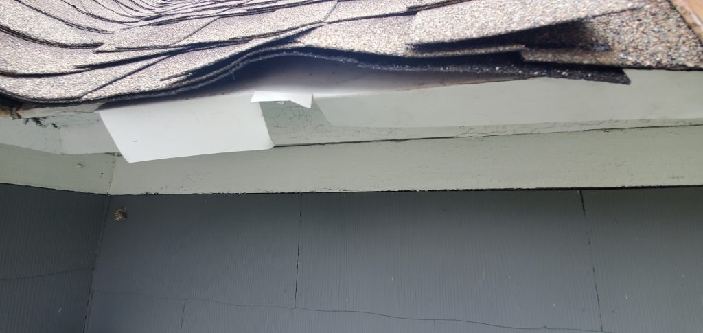 This a close up view of white drip edge that is not correctly installed.