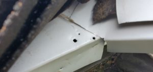 This is a close up of white drip edge at the corner of a roof.