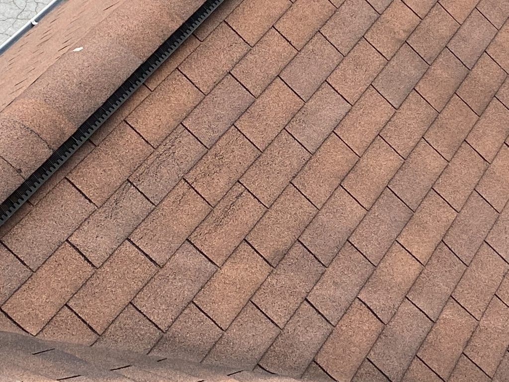 This is an up close image at the ridge of the roof showing damaged, creased shingles.