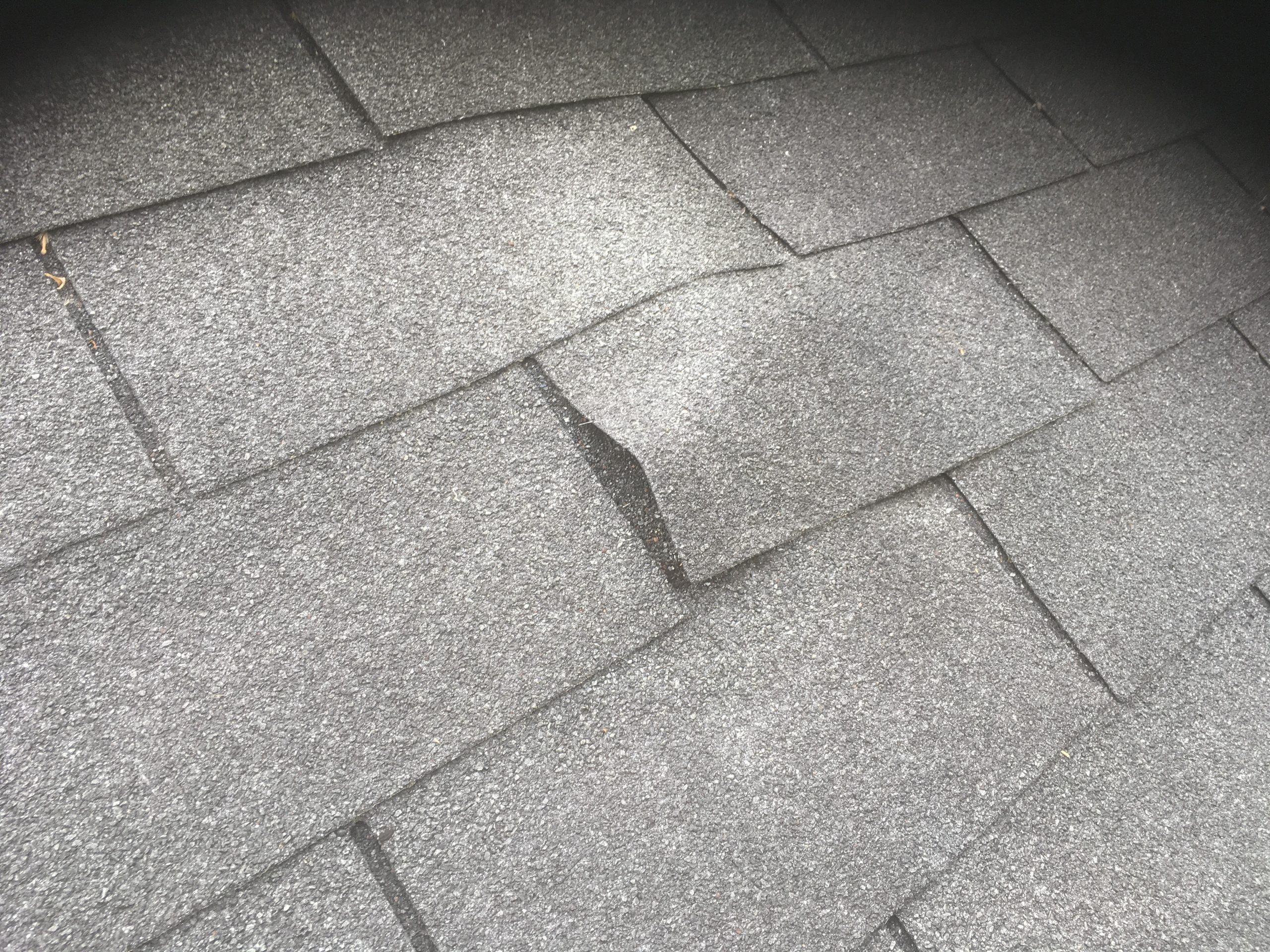 This is a picture of black shingles that has bad board beneath it.