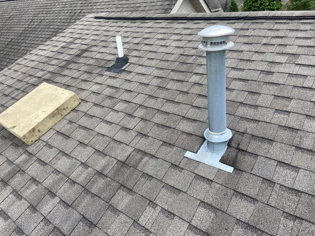 this is a picture of the roof pipe that is leaking and of a metal exhaust pipe coming through a grey colored roof