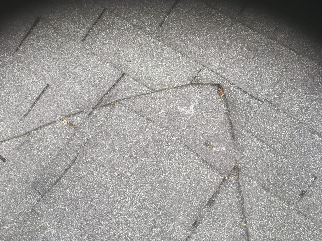 This is a picture of gray shingles that was repaired incorrectly.
