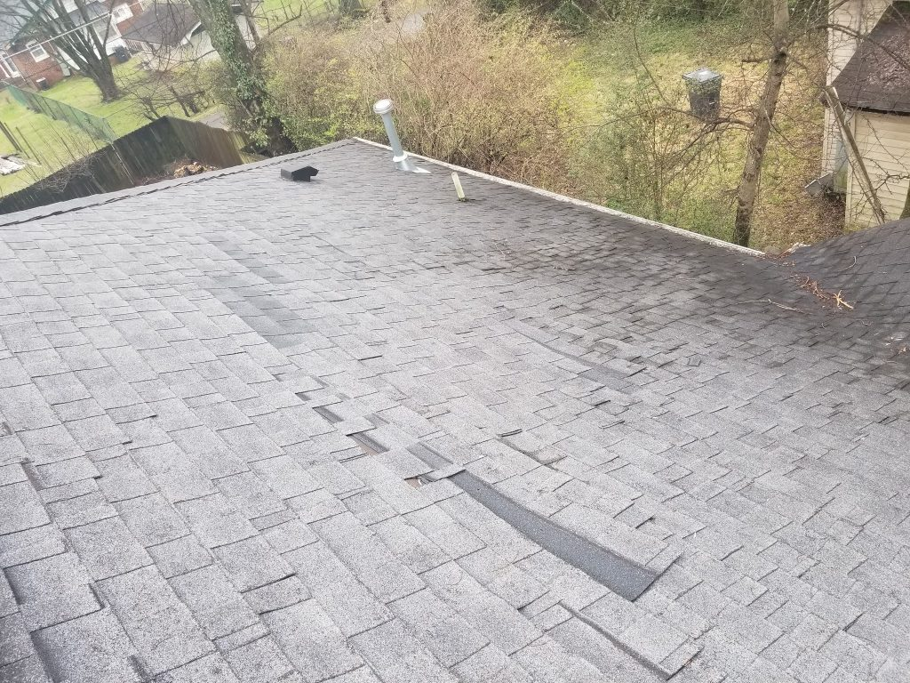 This is a view of the roof with gray shingles. Shingles are sliding out of position.