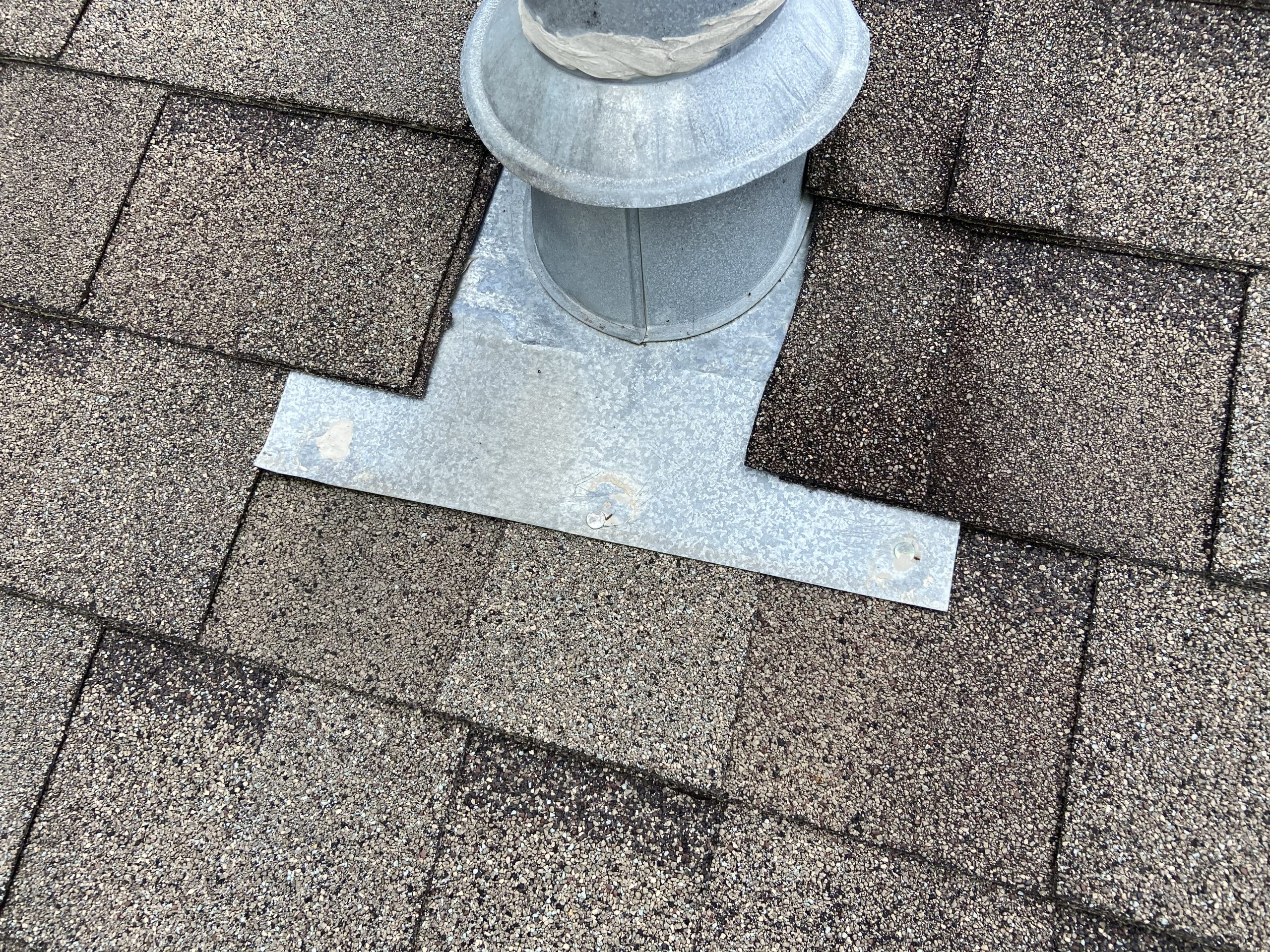 this picture shows a metal pipe collar on a roof and the nails of the pipe collar have caulking on them to prevent leaking