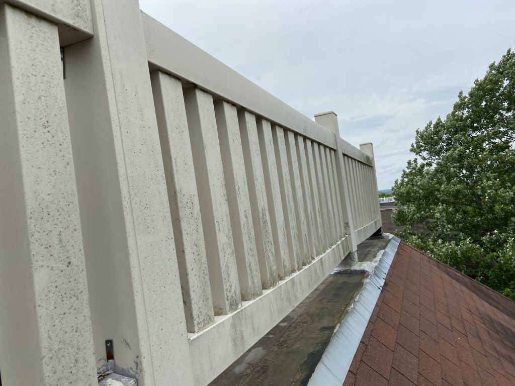 White vinyl railing that is loose on the flat roof portion of roof.