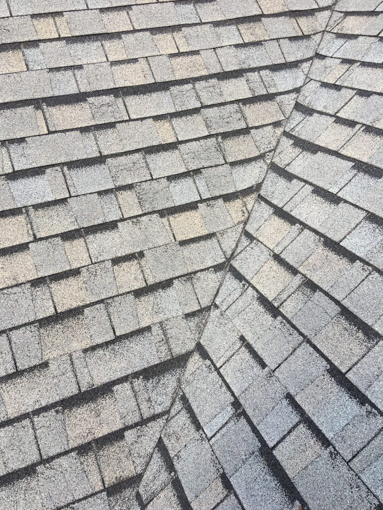 This is a view of 3 tab shingles in gray with hail damage.