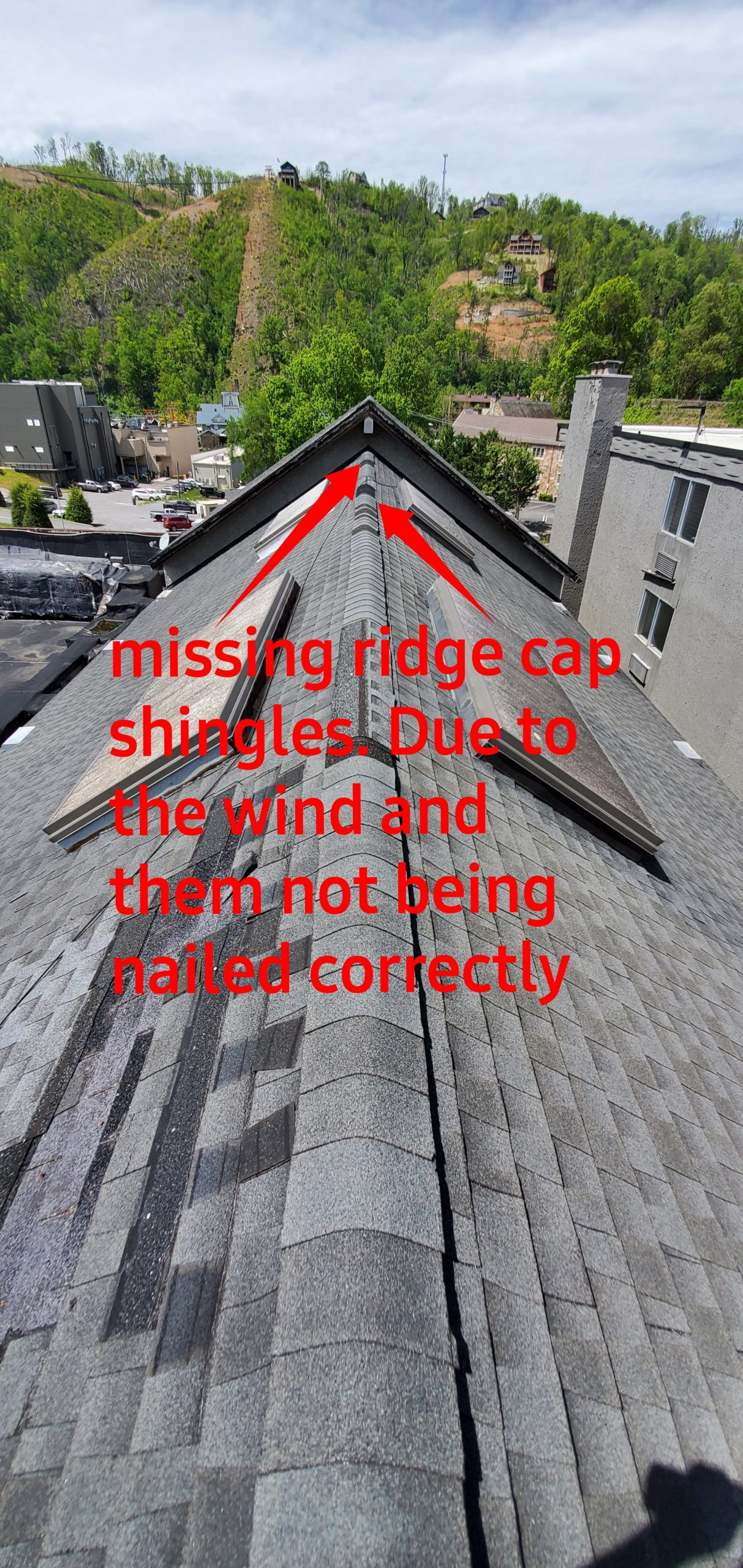 This is a vew of the ridge of the roof with missing ridge cap shingles.