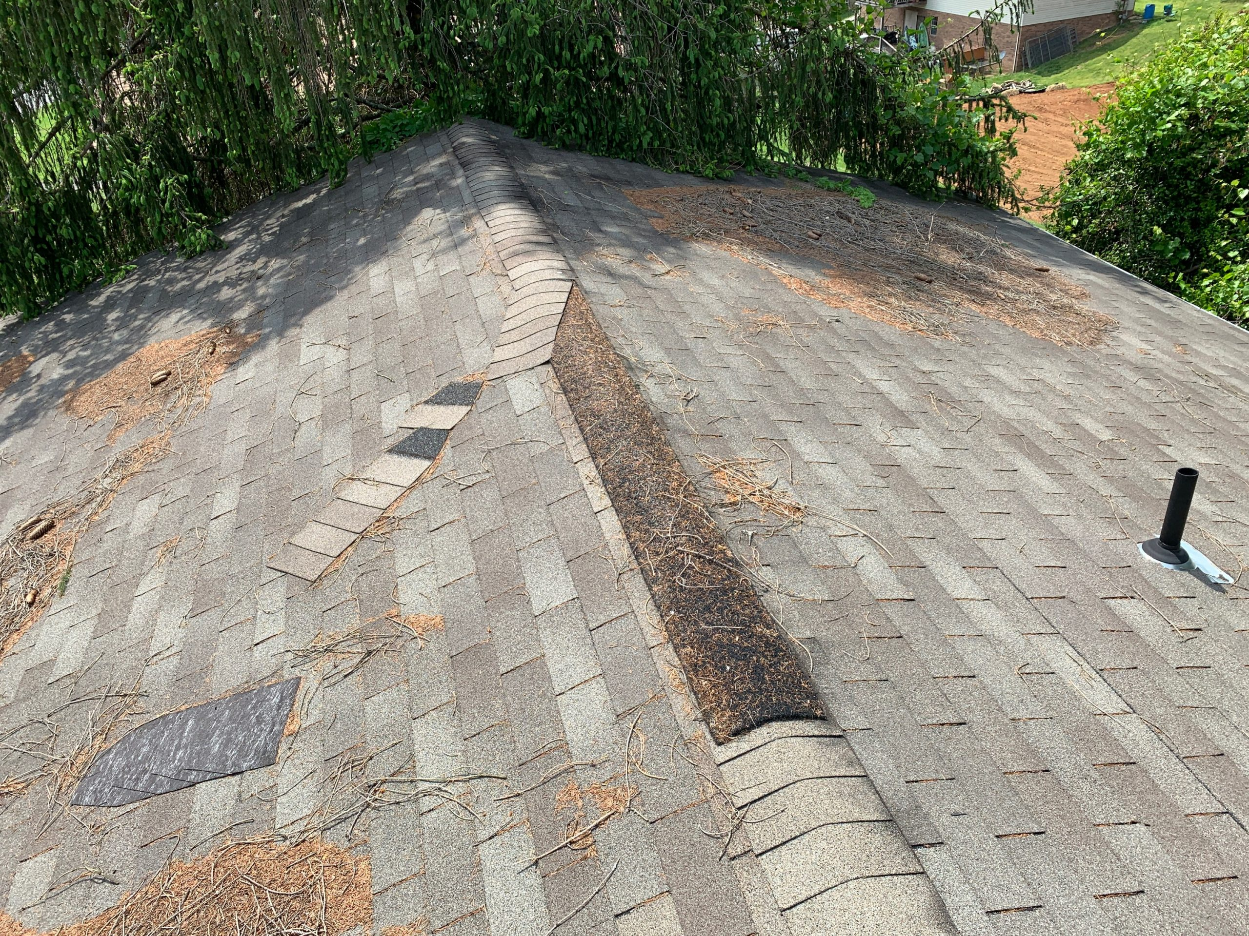 This is a picture of the ridge of the roof with missing ridge cap shingles.