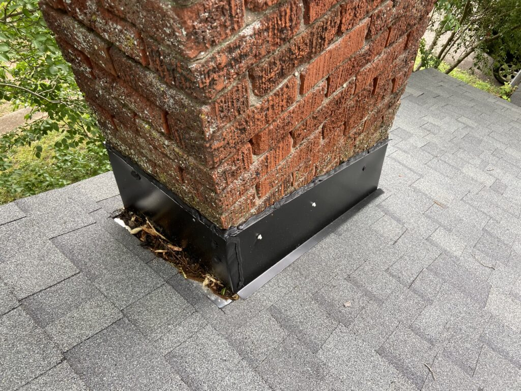 this is a picture of the second chimney on this roof project and it shows black colored counter flashing on a brick chimney