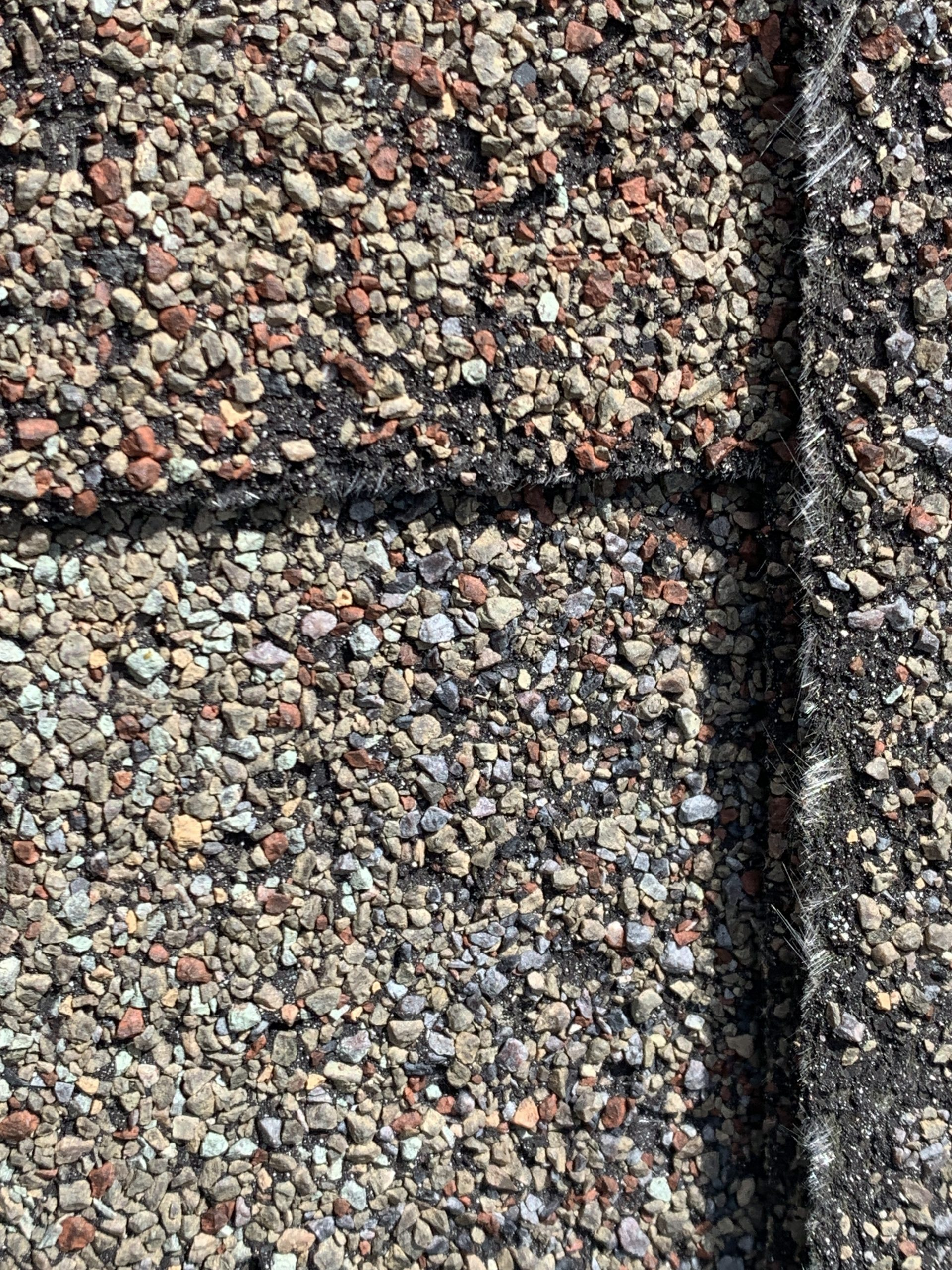 this is a picture showing the condition of this roof there are missing granules on this roof and exposed fiberglass