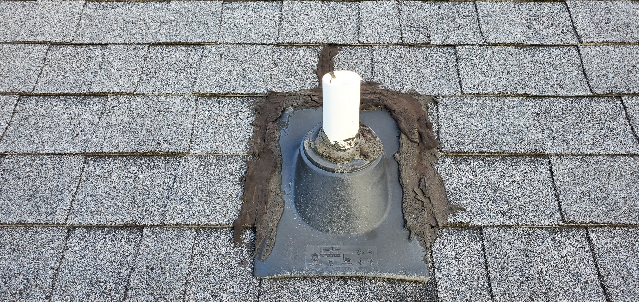 this is a picture of a pipe boot on a roof that was mis installed and has a lot of caulking and roofing cement around it