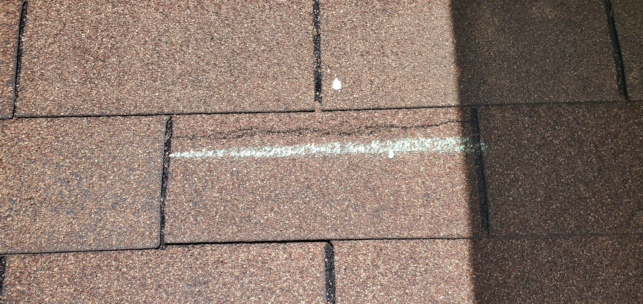 this is a picture of a chalk mark on a roof showing a shingle that has been wind damaged in knoxville tn