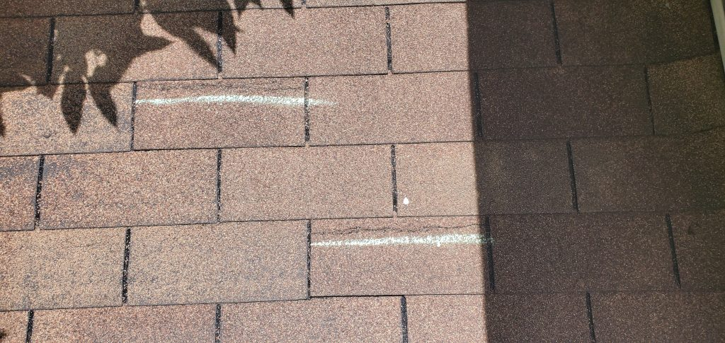 this is a picture of 2 wind damaged shingle that both have chalk pointing out the storm damages to this roof