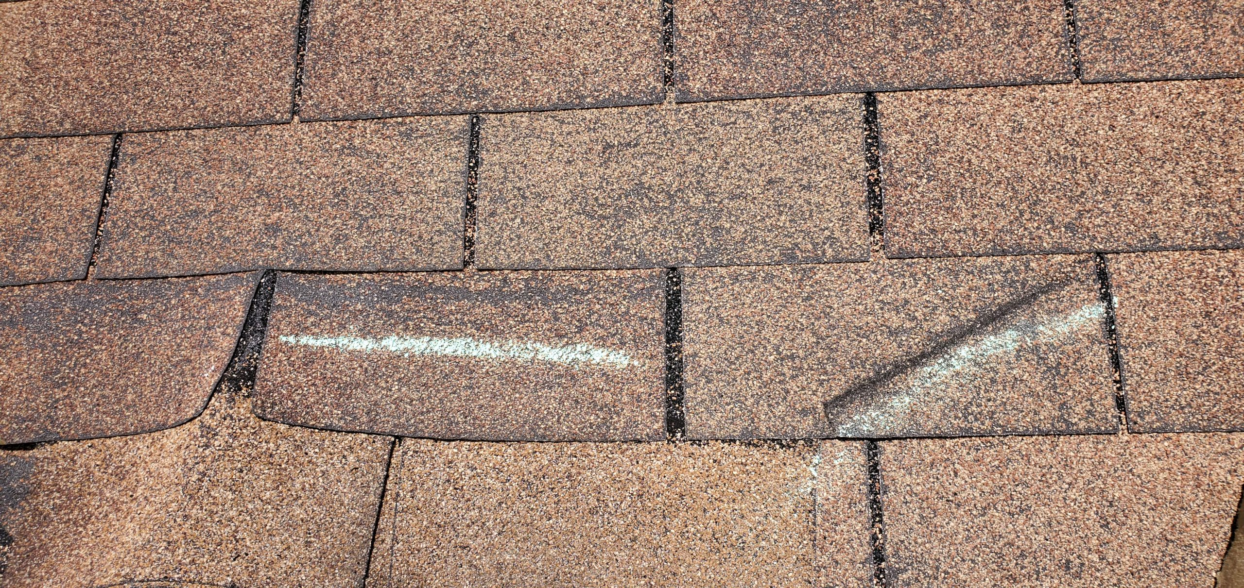 this is a picture of 2 wind creased shingles that are considered storm damaged by the insurance companies