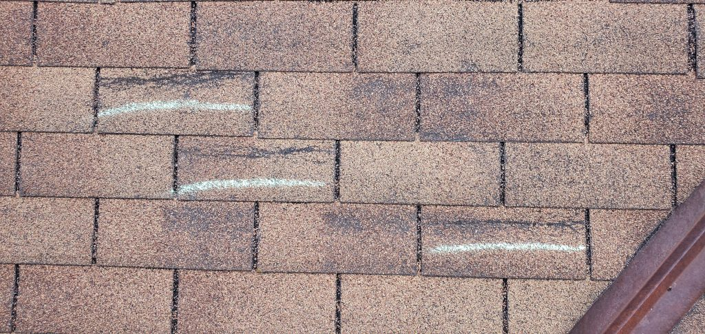 this is a picture of several wind damaged and blown off shingles on a roof in knoxville tn