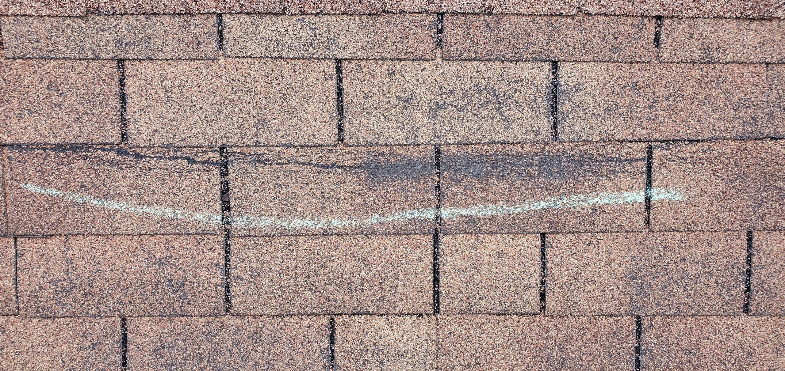 this is a picture of wind damaged section of shingles