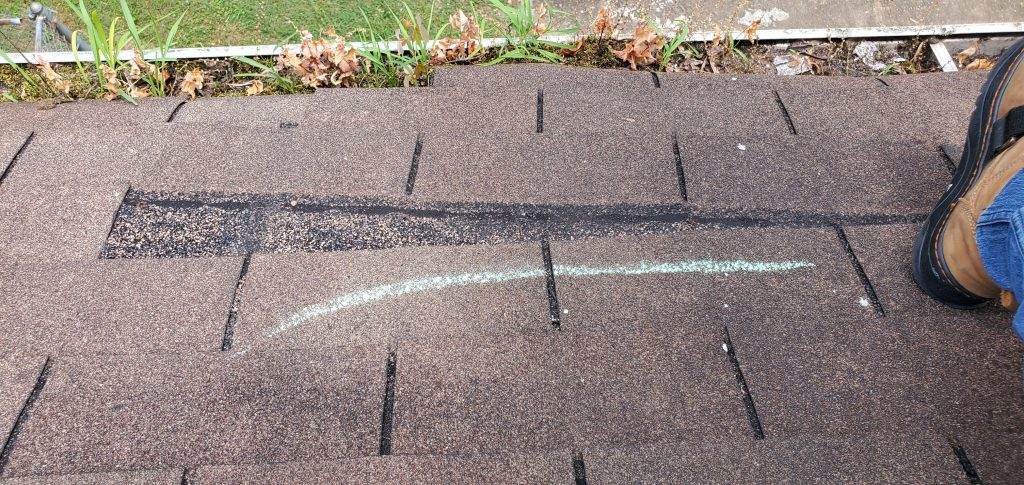 a picture of a hickory colored shingle that is wind damaged in knoxville tn