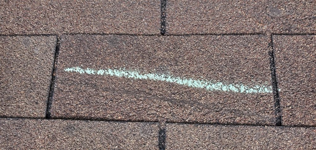 this is a picture of a storm damaged shingle it is storm damaged from the wind