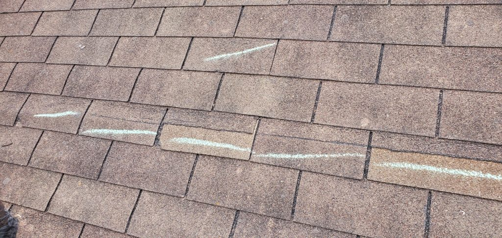 this picture shows some sort of a cut along several roofing shingles