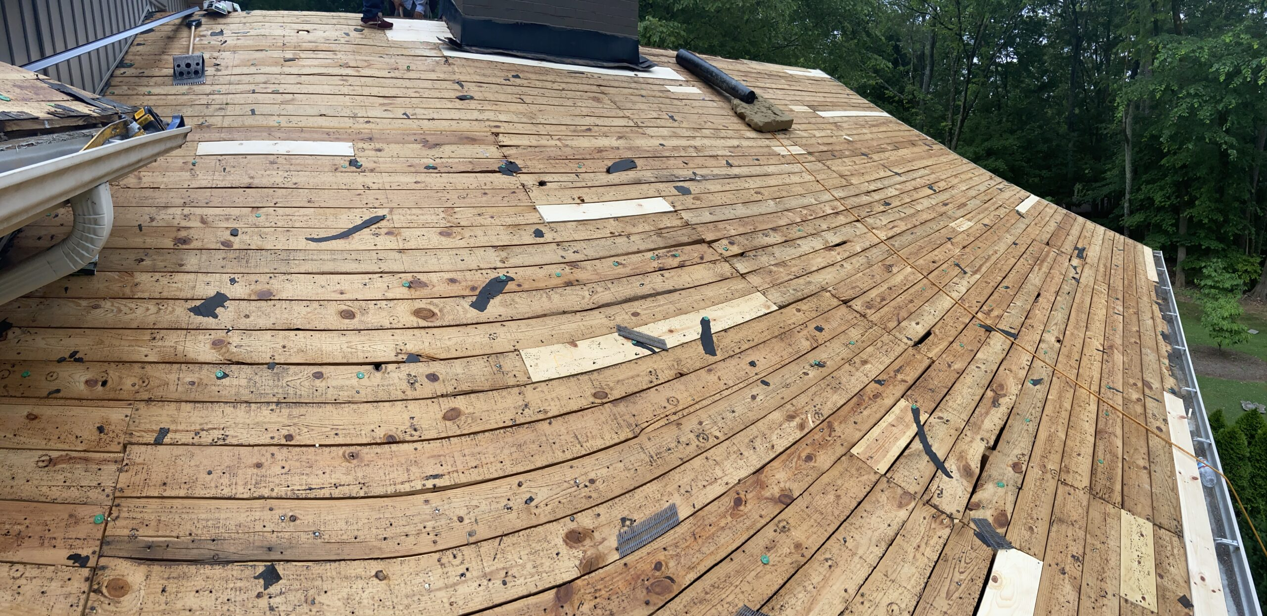 This is a picture of a lot of bad deck boards on a roof that are being replaced with new 1x6 wood