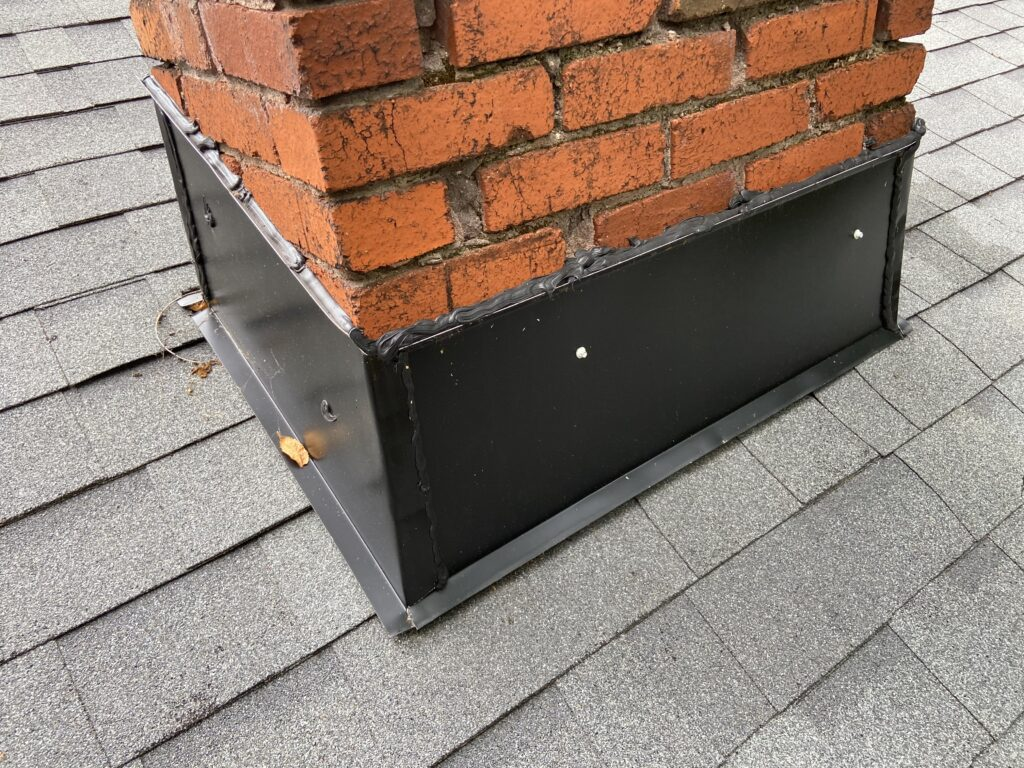 this is a picture of new black colored counter flashing installed on a brick chimney
