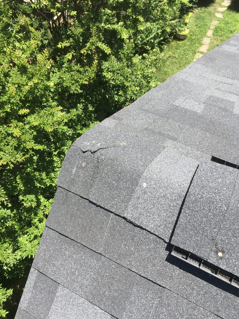 This is a view of the ridge of the roof with a black cracked shingle.