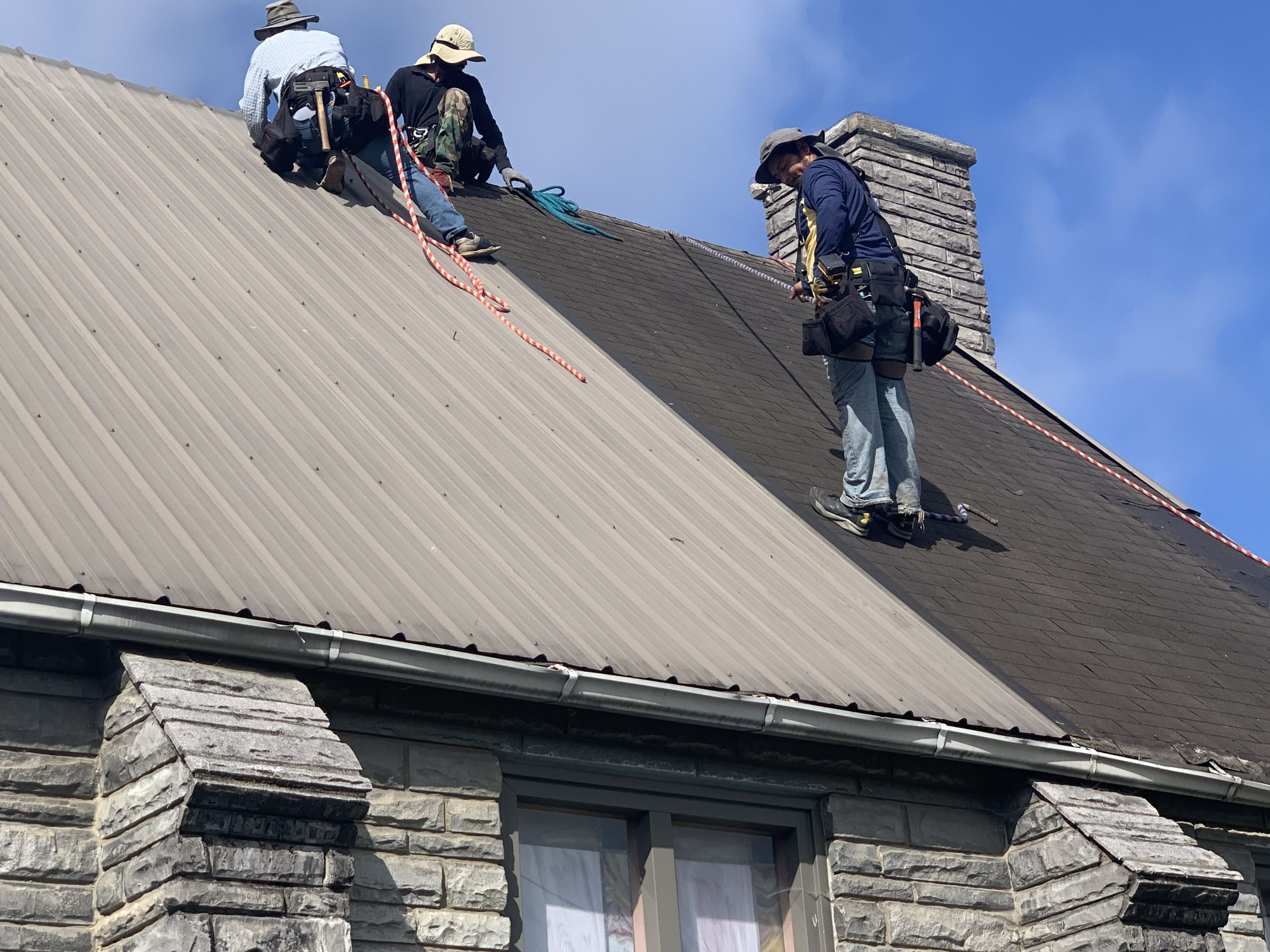 This is a view of the roof installers working on the roof of the church.