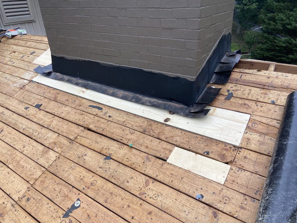 This is an up close view of deck boards and chimney flashing.