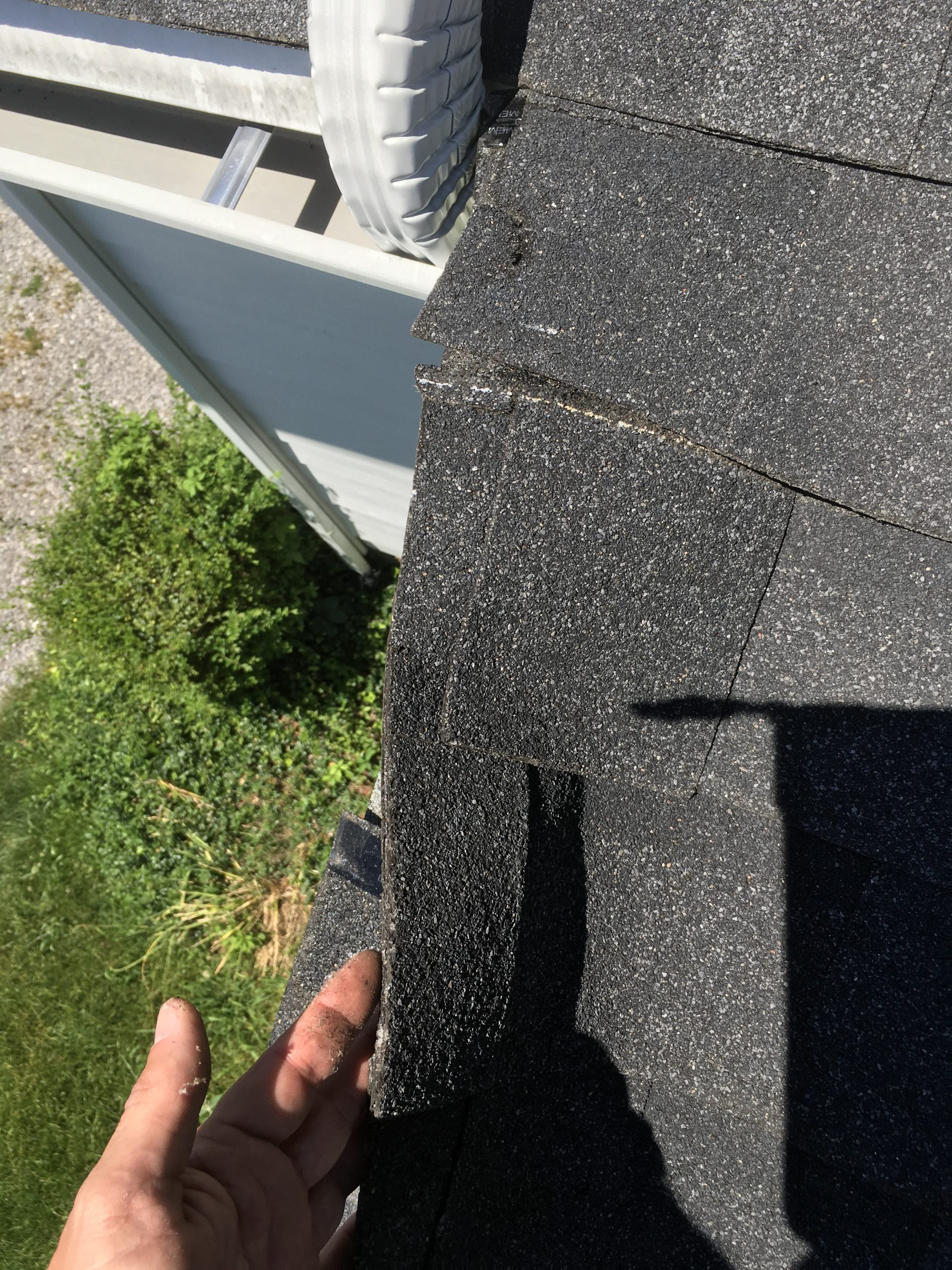 This is a view of the roof  edge with black shingles.