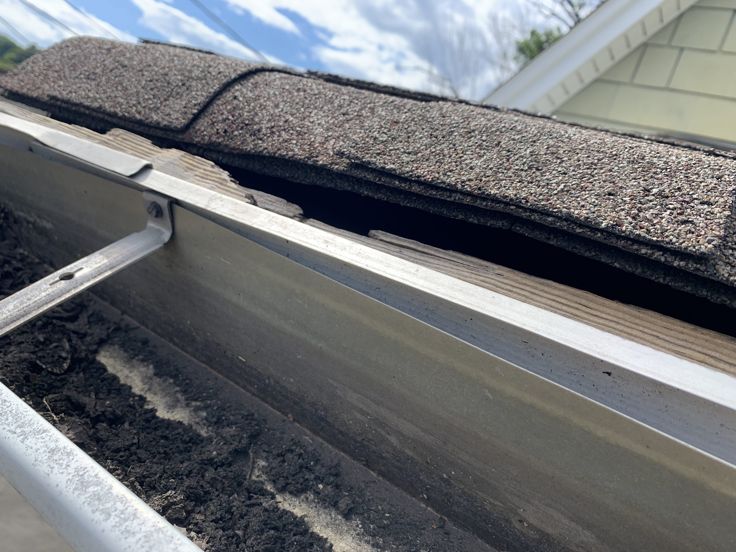 this is a picture of the edge of a roofline where there is no drip edge and the shingles are bending over the edge of a roof