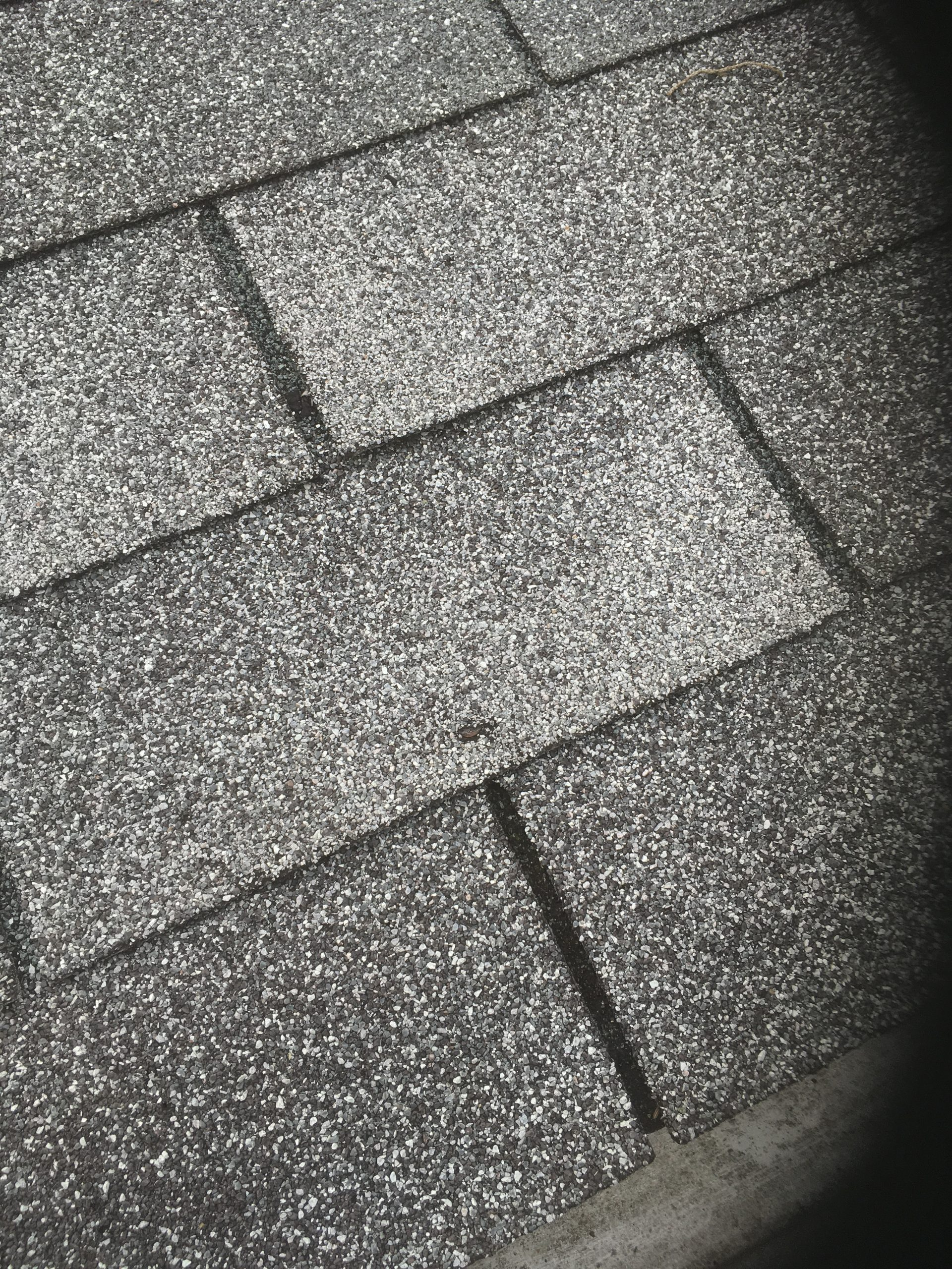 this is a picture of gray shingles with a nail poking or popping through the shingles