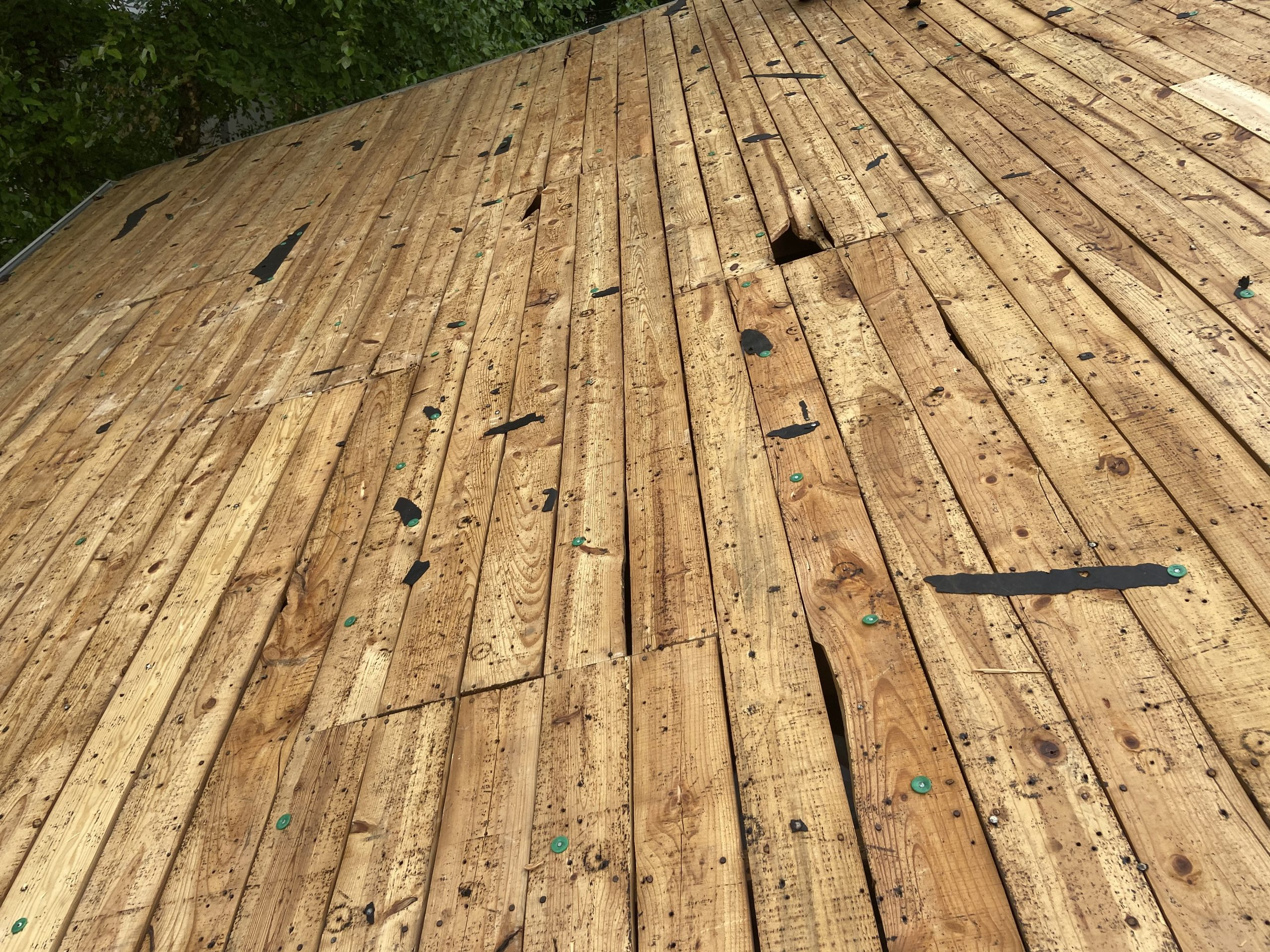 This is a view of the roof deck boards with certain areas with damage.