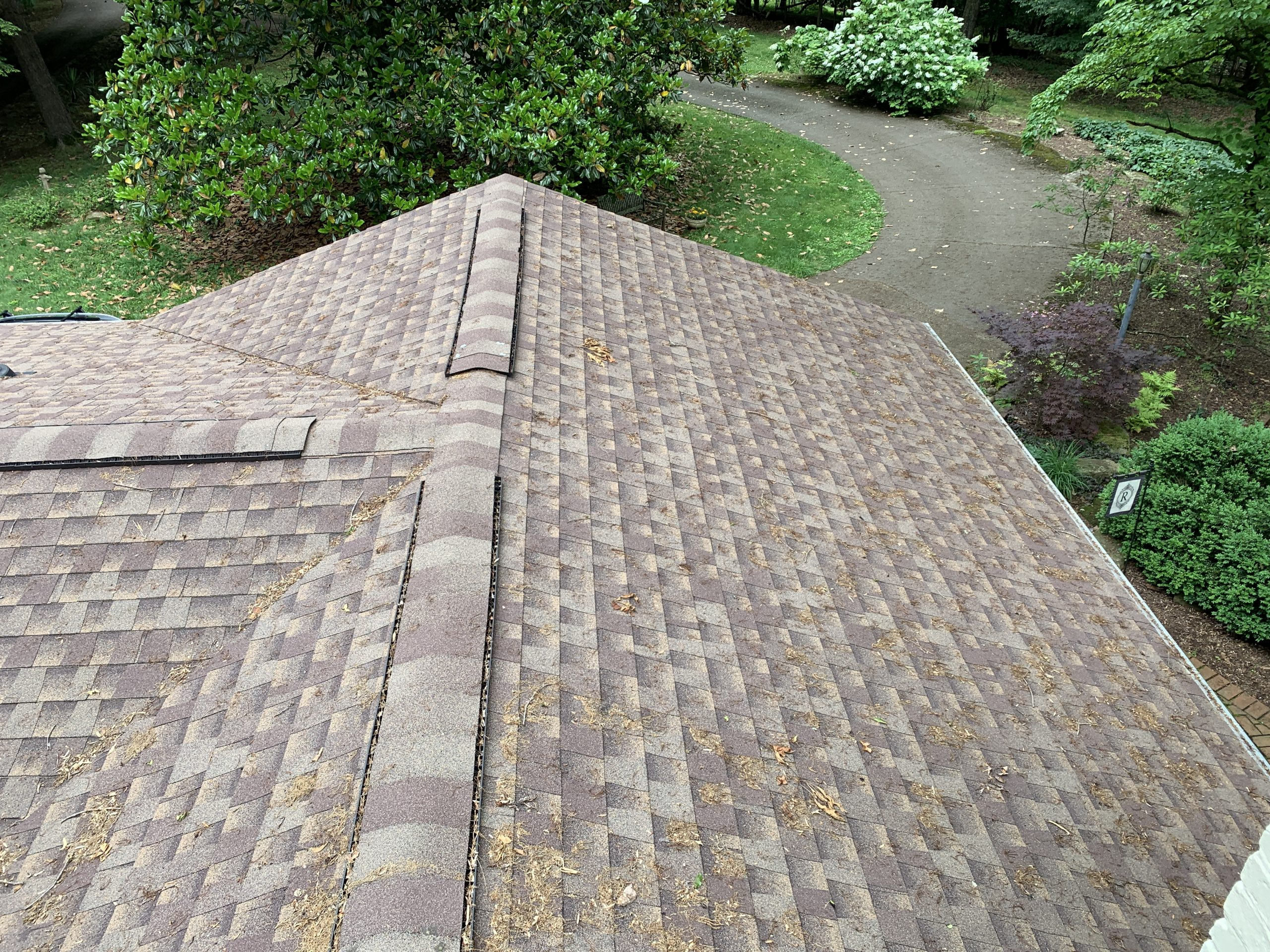 This is a view looking at a ridge of the home. The shingles are weathered wood in color.