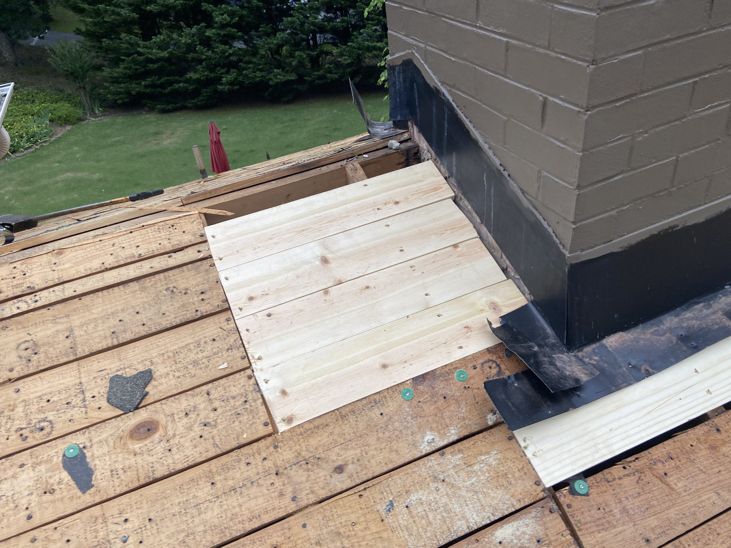 This is a view of new deck boards installed and counter flashing at the chimney.