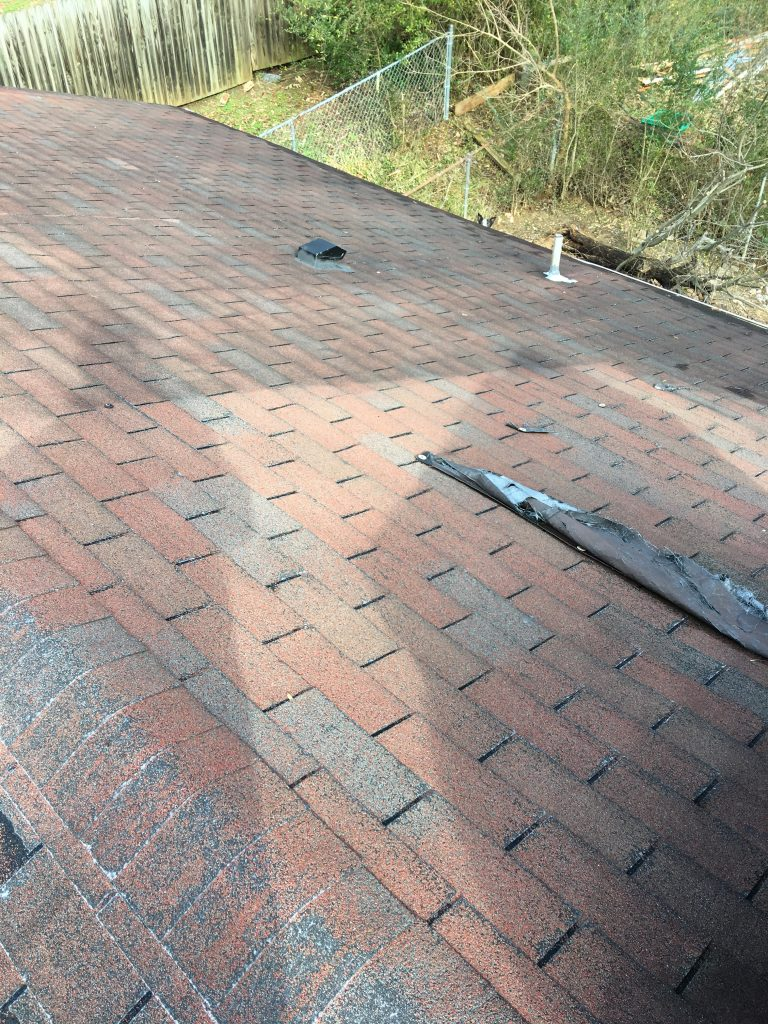 This is a picture of the slope of the roof with a pipe boot and the remnants of a tarp that is left on the roof.