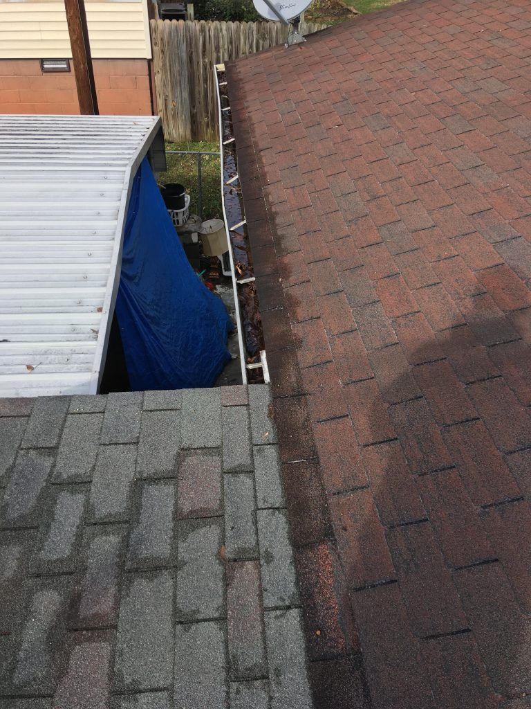 This is a picture of the edge of the roof with gutters.  In the gutters is standing water and debris.