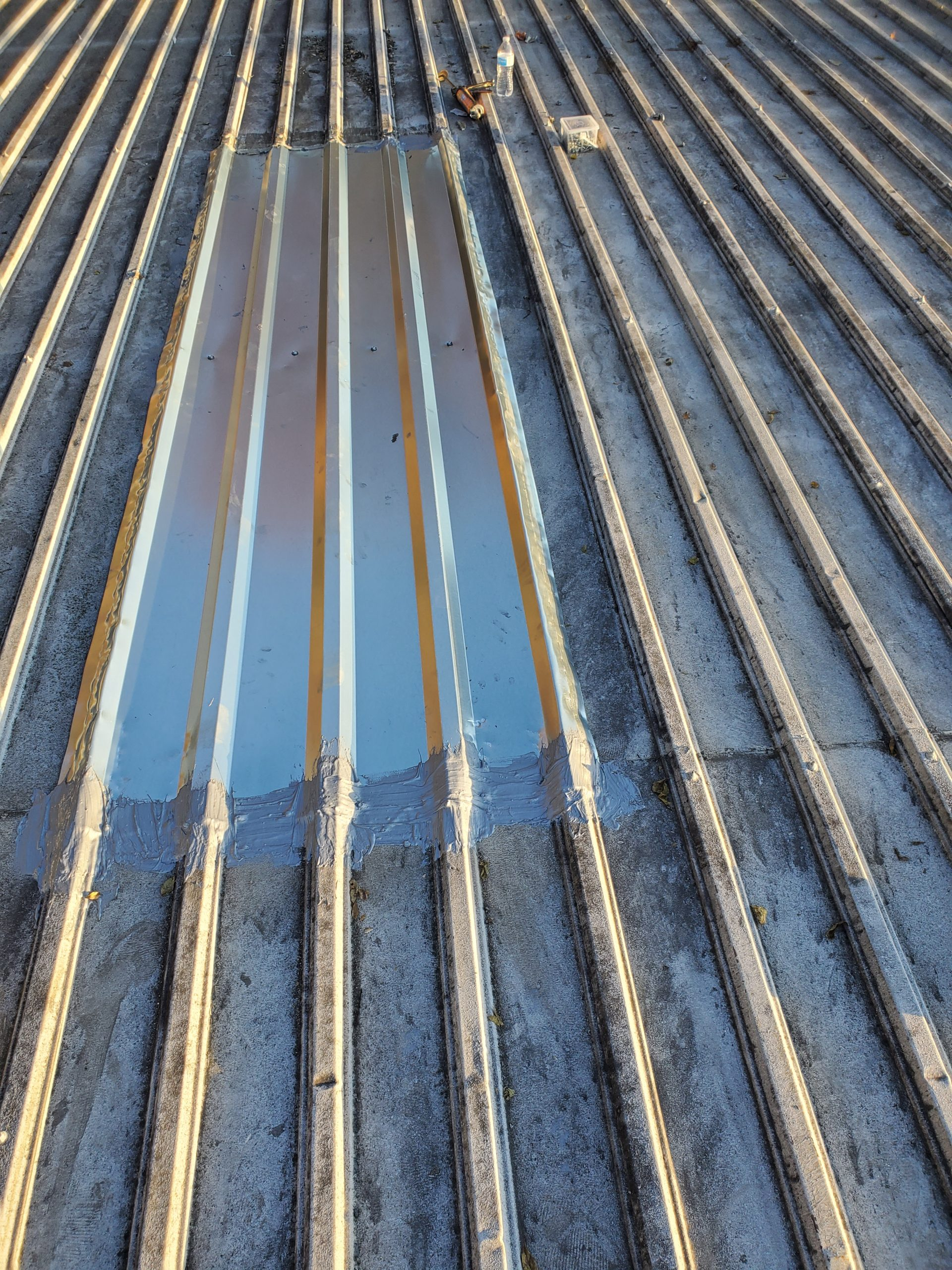 This is a view of the skylight on a metal roof sealed over with Aldo 385.